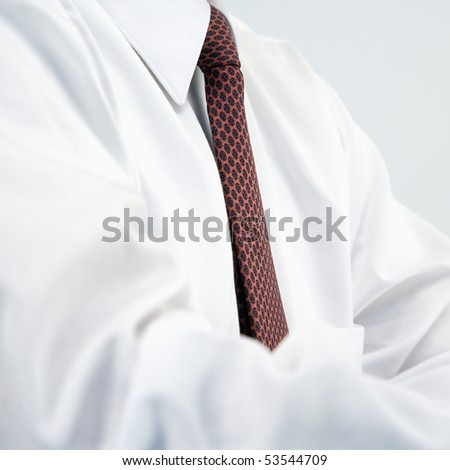 Detail of businessman wearing white dress shirt and necktie.