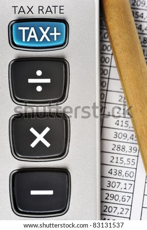 Detail of calculator, focusing the TAX key, next to a sheet of paper with numbers and a pencil.