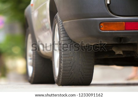 Detail of car, wheels with aluminum discs and new black rubber tire protector on light blurred background. Transportation, safety, reliability, modern design concept. #1233091162