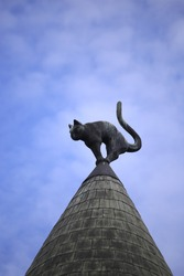 Detail of Cat House in Riga, Latvia. Bronze black cat on top of a roof.