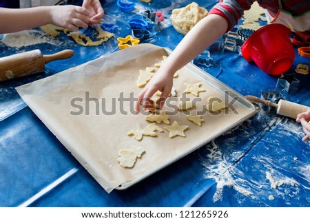 Detail of child's hands cutting Christmas cookies