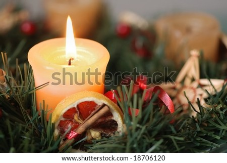 Detail of christmas advent wreath with burning candle. Focus on candle.