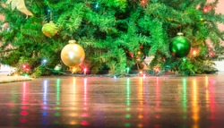 Detail of Christmas tree decorations with lights reflections on the floor - Cropped composition for holidays background