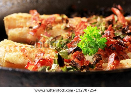 detail of codfish fillet fried in a pan