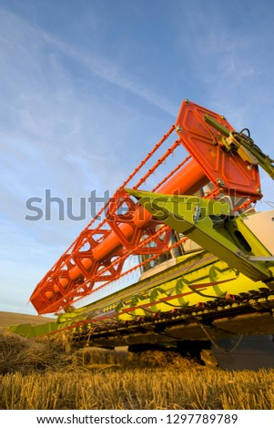 Detail of combine harvester blades in farm field of harvested wheat #1297789789