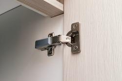detail of concealed hinge on cabinet door, furniture fitting hardware for cupboard or wardrobe