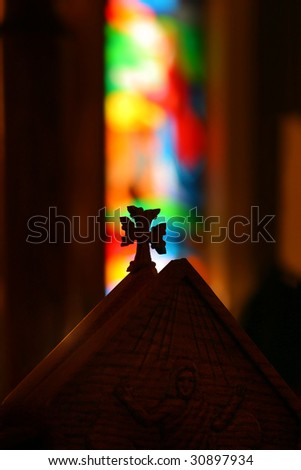 Detail of cross on church pew in front of blurred stained glass behind