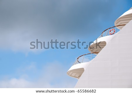detail of cruise ship against partly cloudy and blue sky as travel background
