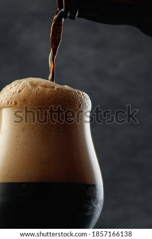 Detail of dark beer with overflowing foam head. Stream of dark stout pours into a beer glass Stock photo ©