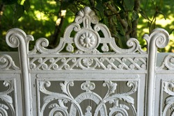 Detail of decorative white Victorian wrought iron bench with garden foliage in the background