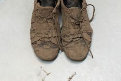 Detail of dirty dried muddy and messy sneaker shoes totally covered with mud looking unrecognizable while laying on the floor