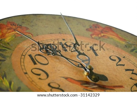 Detail of dusty old clock reading almost 12 o'clock shallow depth of field on white background. The clock is decorated in a tole painting style design in fall colors of gold and orange with green