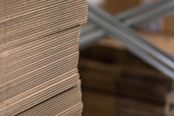 Detail of edge of neatly stacked corrugated cardboard for making boxes, with metal factory shelves in background in soft-focus