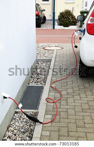 Detail of electric car charging battery from house wall jack