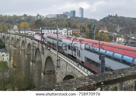 Detail of electrical railroad in Luxembourg city with train, rails, contact lines and viaduct structures in dark autumn day illustrating urban transport concept, Luxembourg.