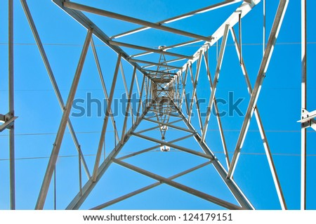Detail of electricity pylon against blue sky: high voltage electric pillar from below