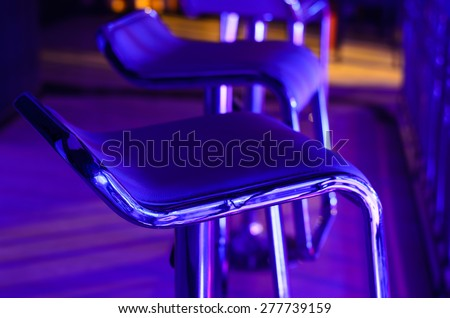 Detail of Empty Bar Stool Lit in Purple Blue Light at Night Club or Bar