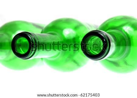 Detail of empty green glass wine bottles on white background.