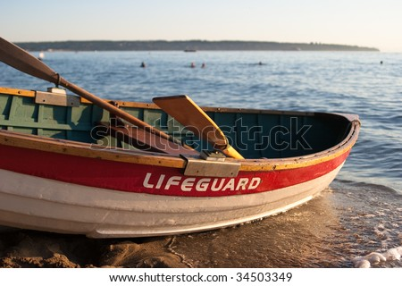 Detail of empty lifeguard rowboat on beach at sunset