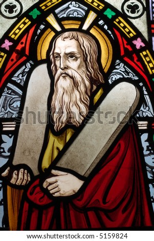 Detail of English, Victorian stained glass church window depicting Moses with the tablets of covenant in his arms, interestingly without text, means he is pictured before climbing Mount Sinai