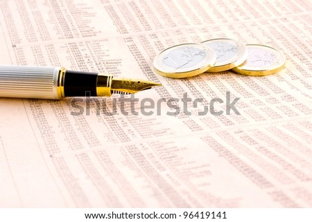detail of euro coins and a golden pen  on the financial newspaper