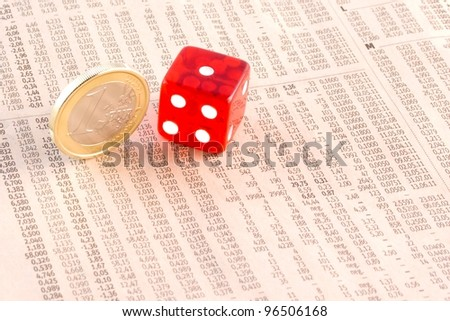 detail of euro coins and a red dice on the financial newspaper
