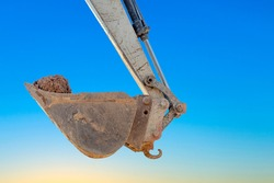 detail of excavator bucket filled with soil  under blue sky