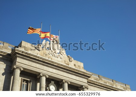 Detail of Facade of Barcelona's City Council with flags flying at half mast as a sign of mourning.