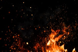 Detail of fire sparks isolated on black background. Abstract flaming background