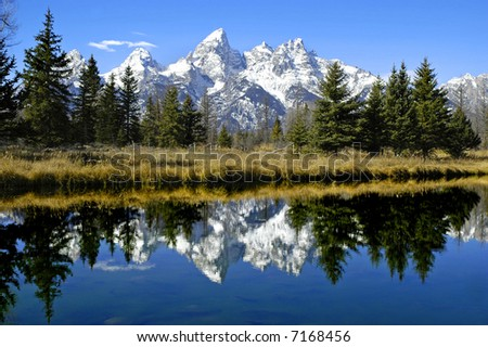 Detail of Grand Tetons Mountains with blue sky with reflection in river