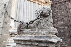 Detail of granite lion with iron chain in the door of The Cathedral of the Saviour (Catedral de Cristo Salvador), Catholic church in Avila in the south of Old Castile, Spain.