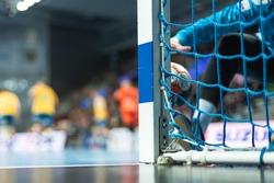Detail of handball goal post with net and handball match in the background.