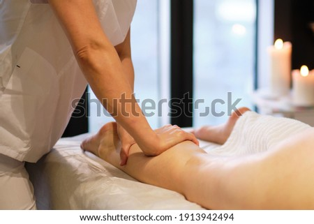 Detail of hands massaging human calf muscle.Therapist applying pressure on female leg. Hands of massage therapist massaging legs of young woman in spa salon. Body care in spa salon for young woman.
