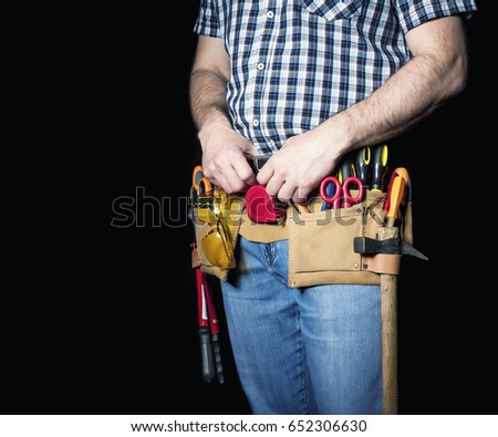 detail of handyman with leather toolsbelt and tools on dark background #652306630
