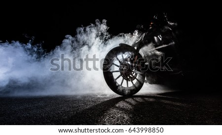 Detail of high power motorcycle chopper with man rider at night. Fog with backlights on background.