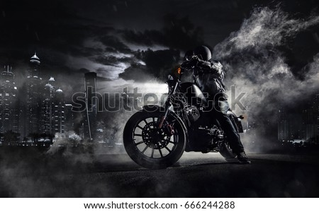 Detail of high power motorcycle chopper with man rider at night. Modern city of Dubai and fog with backlights on background.