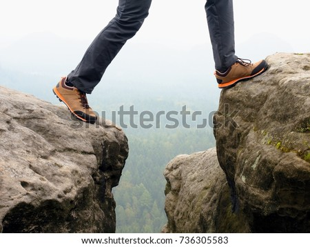 Detail of  hiker legs in black orange hiking boots on mountain summit. Feet in trekking shoes and legs  light trousers  on background of the peaks #736305583