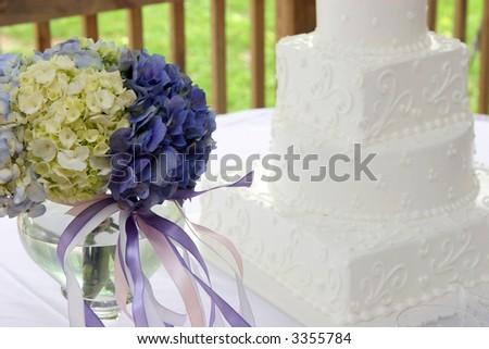 Detail of hydrangea bouquet with wedding cake.