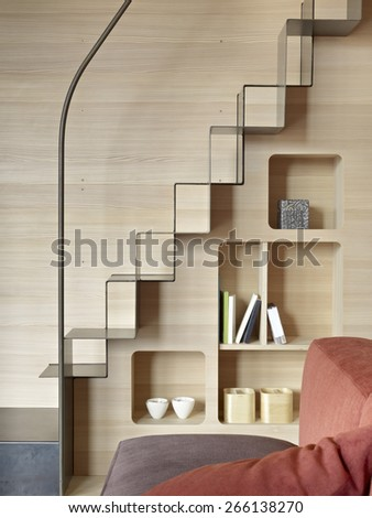 detail of iron staircase with bookcase in the living room with wood paneling