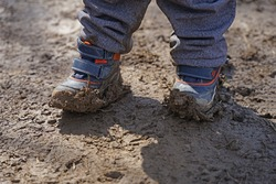 Detail of kids muddy boots, boy child in dirty hiking shoes during outdoor activity concept