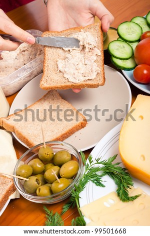 Detail of kitchen table with food and female hands making tuna sandwich.