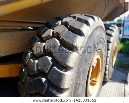 Detail of large tyre big wheels of heavy truck. Heavy duty vehicle wheel detail. Tire structure on large yellow working lorry.