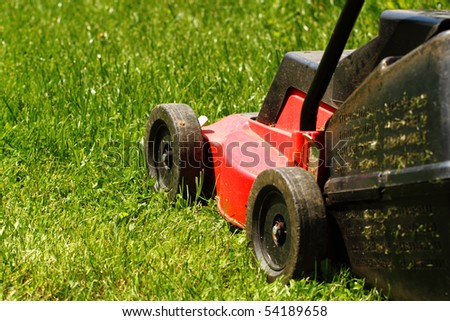 Detail of lawnmower on green grass in sunny day