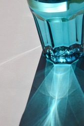 detail of light reflections of a blue waterglass in the sun on white background