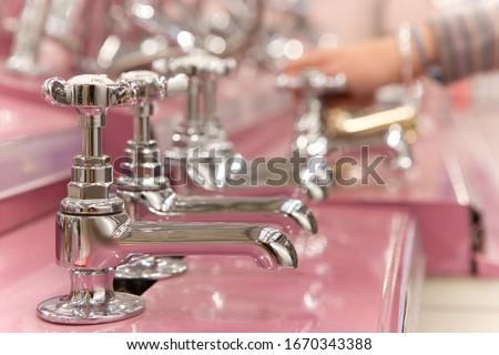 Detail of man choosing taps in plumbing department of hardware store