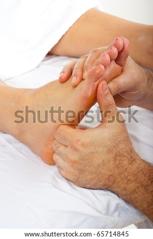 Detail of man hands doing reflexology massage to woman feet