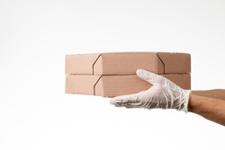Detail of man with gloves holding pizza box for takeaway isolated on gray background. Delivery concept. Delivery service concept. Copy space.