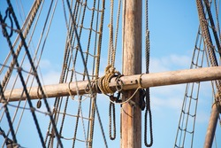 Detail of mast of historic wooden sailing ship, with rigging and ropes, blue sky and copy space.