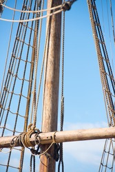 Detail of mast of old historic wooden sailing ship, with rigging and ropes, blue sky and copy space.