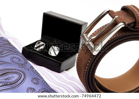 detail of men's accessories: tie, shirt, belt, studs on white background